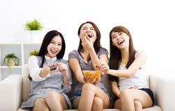 grupo da jovem mulher que come petiscos e que olha a tevê Imagens de Stock Royalty Free