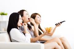 grupo da jovem mulher que come petiscos e que olha a tevê Imagem de Stock Royalty Free