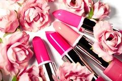 Grupo da mola de batons em flores cor-de-rosa Coleção do cosmético da beleza A forma tende nos cosméticos, bordos brilhantes Imagens de Stock Royalty Free