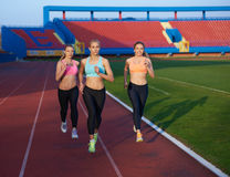 Grupo da mulher do atleta que corre no autódromo do atletismo Foto de Stock