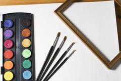 Grupo da pintura da aquarela, quadro de madeira e escovas no fundo branco do álbum Fotografia de Stock