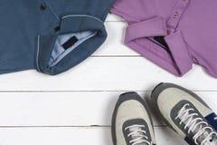 Grupo da roupa e das sapatas dos homens no fundo de madeira Esportes t-shirt e sapatilhas em cores brilhantes Vista superior Imagem de Stock