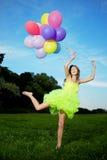Grupo da terra arrendada da mulher de balões de ar coloridos Fotografia de Stock