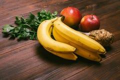 Grupo das bananas, da raiz de aipo e das maçãs do vermelho em Ta de madeira escura Fotos de Stock Royalty Free