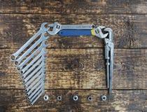 Grupo das chaves combinadas e de chaves ajustáveis velhas em um fundo de madeira velho Foto de Stock
