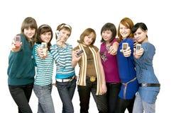 Grupo das meninas que mostram telefones móveis Fotografia de Stock