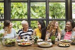 Grupo das mulheres da diversidade que pendura comendo junto o conceito imagens de stock