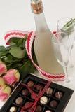 Grupo das rosas, da garrafa do champanhe, dos vidros de vinho e da caixa sortido do chocolate Foto de Stock