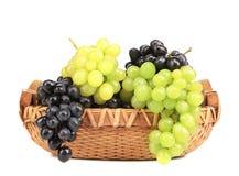 Grupo das uvas brancas e pretas em uma cesta fotos de stock