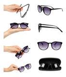 grupo de óculos de sol plásticos à moda diferentes com a mão isolada no fundo branco foto de stock royalty free