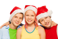 Grupo de adolescencias de los amigos junto en casquillos de Navidad Papá Noel Imágenes de archivo libres de regalías