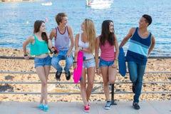 Grupo de adolescencias diversas de la raza mixta que cuelgan hacia fuera en la playa Imagen de archivo libre de regalías