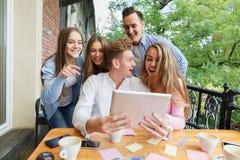 Grupo de adolescencias usando la tableta en un fondo del café Amigos felices con la tableta Concepto moderno de la forma de vida Imagen de archivo
