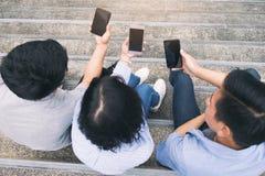 Grupo de adolescente joven usando los teléfonos móviles Foto de archivo