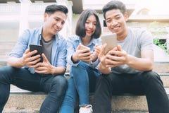 Grupo de adolescente joven usando los teléfonos móviles Imagen de archivo libre de regalías