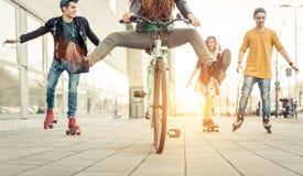 Grupo de adolescentes activos en ciudad cuatro adolescencias que hacen recreationa Fotos de archivo libres de regalías