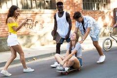 Grupo de adolescentes activos que hacen actividad recreativa en un urb Foto de archivo libre de regalías