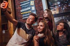 Grupo de adolescentes atractivos sonrientes que llevan el equipo casual que toma el selfie con té de consumición del teléfono móv Imagen de archivo
