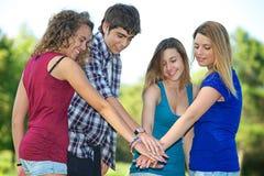 Grupo de adolescentes com mãos na pilha fotografia de stock royalty free