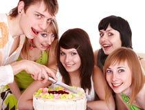 Grupo de adolescentes con la torta del feliz cumpleaños. Fotografía de archivo