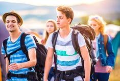 Grupo de adolescentes con las mochilas que llegan el festival de música Imagen de archivo