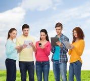 Grupo de adolescentes con smartphones y PC de la tableta Fotografía de archivo libre de regalías