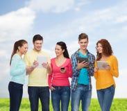 Grupo de adolescentes con smartphones y PC de la tableta Fotografía de archivo