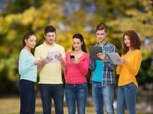 Grupo de adolescentes con smartphones y PC de la tableta Fotos de archivo libres de regalías