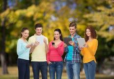 Grupo de adolescentes con smartphones y PC de la tableta Fotos de archivo