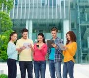 Grupo de adolescentes con smartphones y PC de la tableta Imagen de archivo libre de regalías