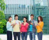 Grupo de adolescentes con smartphones y PC de la tableta Imagen de archivo