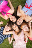 Grupo de adolescentes de las muchachas en parque en hierba Fotografía de archivo