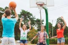 Grupo de adolescentes de sorriso que jogam o basquetebol Fotografia de Stock