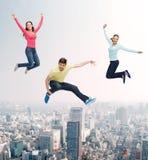Grupo de adolescentes de sorriso que saltam no ar Imagem de Stock