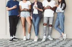 Grupo de adolescentes diversos que usam os telefones celulares exteriores fotos de stock royalty free