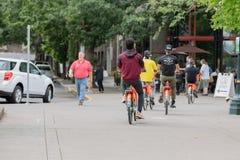 Grupo de adolescentes en las bicis de alquiler fotos de archivo