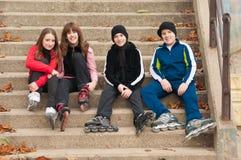 Grupo de adolescentes felices en pcteres de ruedas Imagen de archivo libre de regalías