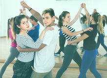 Grupo de adolescentes felices que bailan tango en estudio de la danza Imagen de archivo libre de regalías