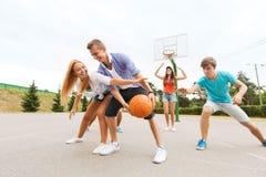 Grupo de adolescentes felices que juegan a baloncesto Imagen de archivo libre de regalías