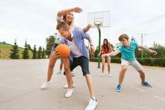 Grupo de adolescentes felices que juegan a baloncesto Foto de archivo