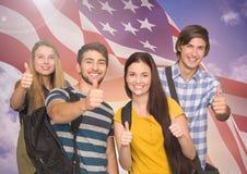 Grupo de adolescentes felices que muestran los pulgares encima de la muestra contra bandera americana fotos de archivo libres de regalías