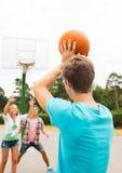 Grupo de adolescentes felizes que jogam o basquetebol Fotografia de Stock