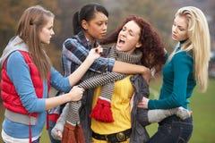 Grupo de adolescentes femeninos que tiranizan a la muchacha Imagen de archivo libre de regalías