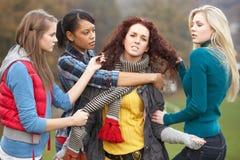 Grupo de adolescentes femeninos que tiranizan a la muchacha Fotografía de archivo