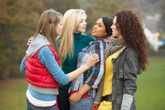 Grupo de adolescentes femeninos que tiranizan a la muchacha Foto de archivo libre de regalías