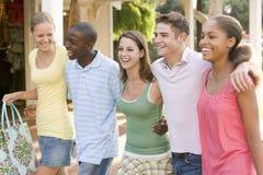 Grupo de adolescentes hacia fuera que hacen compras Imagenes de archivo