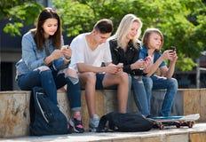Grupo de adolescentes jovenes que se sientan con los teléfonos Foto de archivo libre de regalías