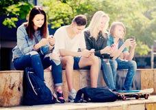 Grupo de adolescentes jovenes que se sientan con los teléfonos Fotografía de archivo libre de regalías