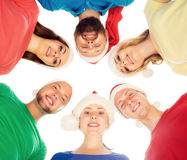 Grupo de adolescentes jovenes y felices en sombreros de la Navidad Foto de archivo