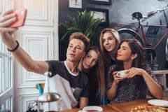 Grupo de adolescentes lindos que toman el selfie con el teléfono móvil mientras que se sienta en un restaurante con el interior e Fotografía de archivo